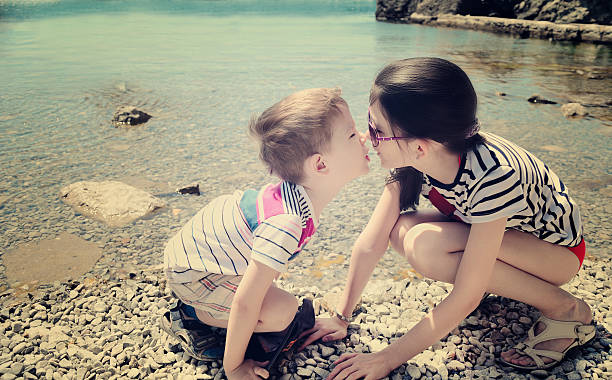 children brother and sister kiss on the beach toning vanilla - little girls little boys kissing love stock photos and pictures