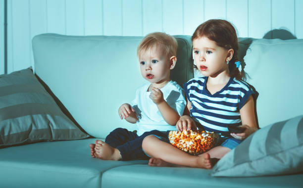 children brother and sister watching tv in evening - filme sehen stock-fotos und bilder