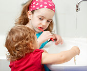 Portrait of two cute little girls, sisters, brushing teeth together in a bathroom. Selective focus to baby girl in front.