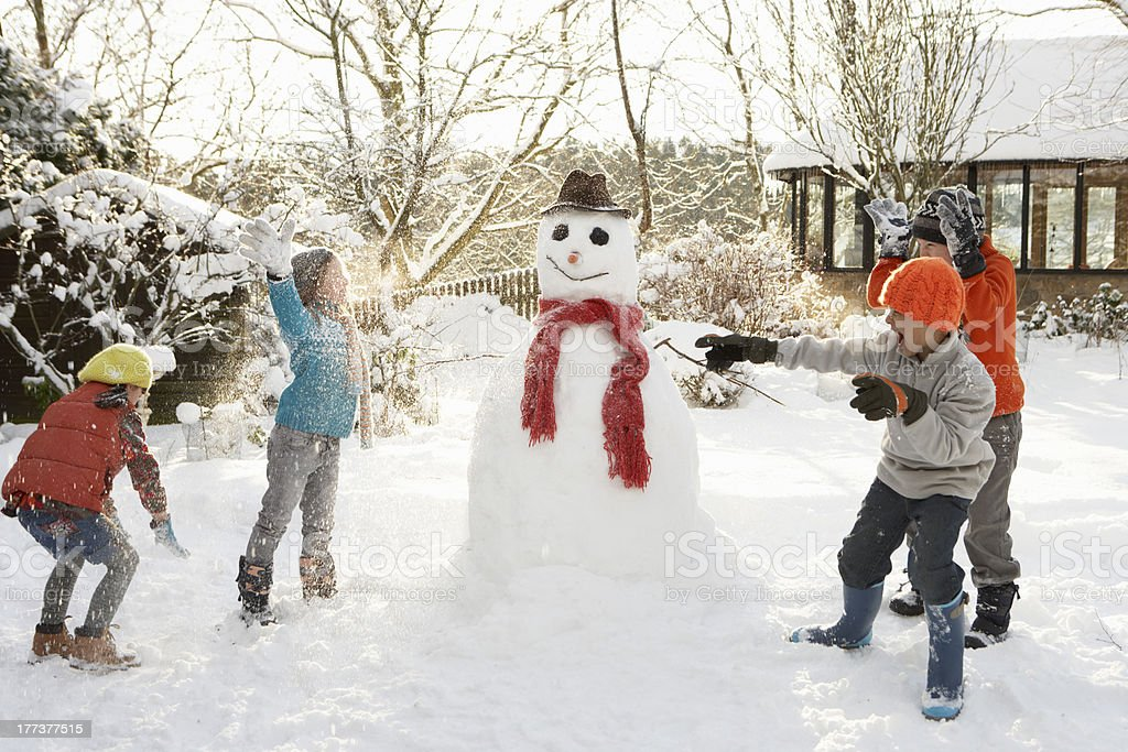 Mãe e filhos construção de um boneco de neve em um jardim - foto de acervo