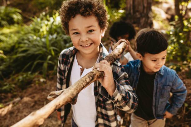 kinderen bouwen kamp in het bos - bos spelen stockfoto's en -beelden