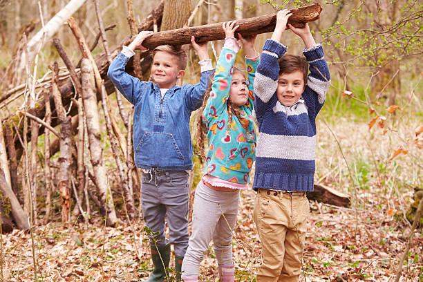 children building camp in forest together - bos spelen stockfoto's en -beelden