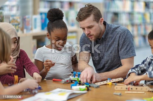 Two (2) kids who are friends are sitting at a table in the library. They are reading a book together as they use it to build their project for class. They are focused and attentive. Their teacher crouches behind them to ensure they are on the right track.