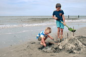 Children Build a Sandcastle at the Beach in Autumn