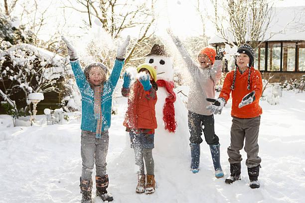 kinder-gebäude schneemann im garten - schneemann bauen stock-fotos und bilder