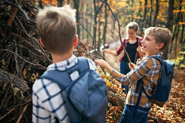 niños edificio palo refugio en el bosque del otoño - boy scout fotografías e imágenes de stock