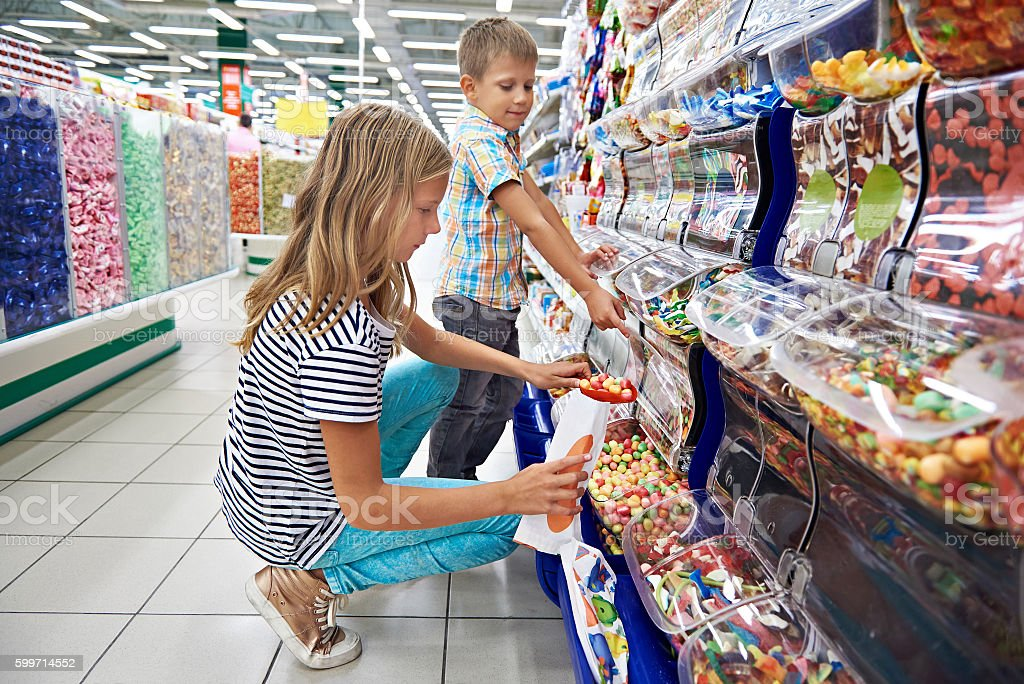Children buy gummi candy stock photo