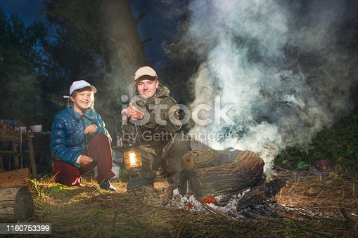 Brother and sister sitting by the fire with a lantern at night