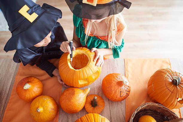 children carving from the pumpkin - schnitzmesser stock-fotos und bilder