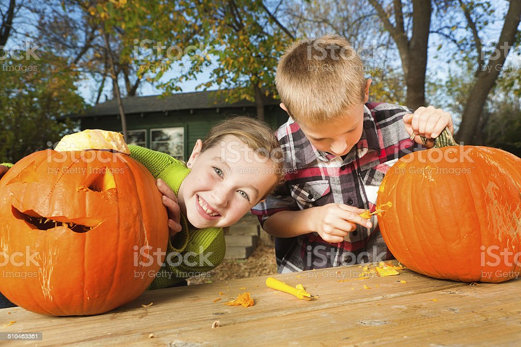 Children Carving Halloween Pumpkins stock photo