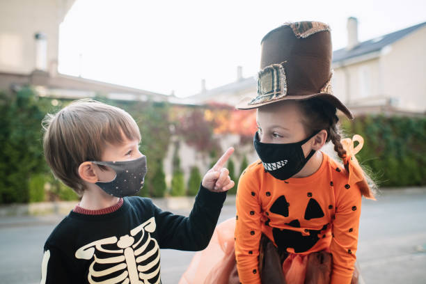 Children celebrating Halloween during COVID-19 pandemic Little girl and boy in protective face masks trick or treating during Halloween halloween covid stock pictures, royalty-free photos & images