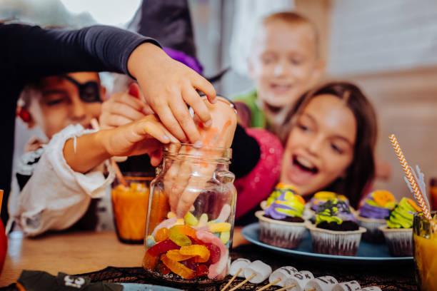 children celebrating halloween in kindergarten laughing while eating sweets - halloween candy стоковые фото и изображения