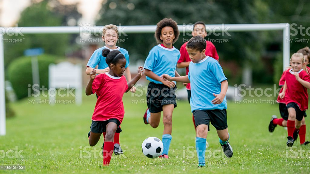 Children Chasing Soccer Ball During a Match stock photo