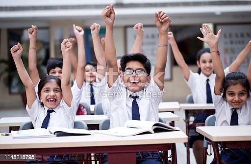 Group of excited school children cheering in classroom