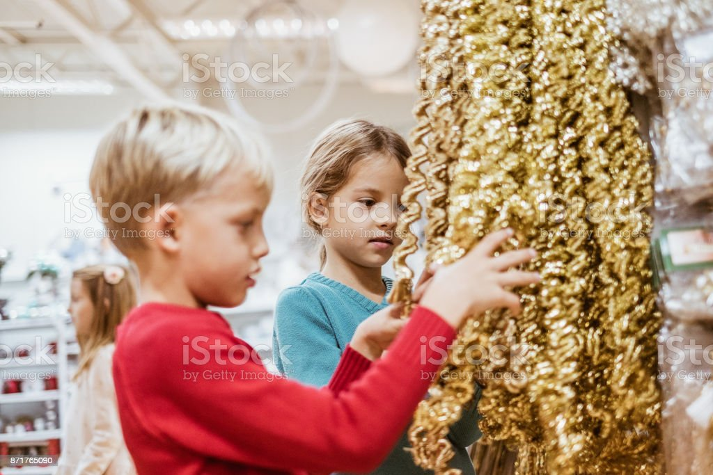 Children chosing christmas decoration in store stock photo