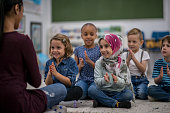 A multi-ethnic group of young school children are indoors in their classroom. They are sitting on the floor and clapping along to music with their teacher. They are smiling and having fun.