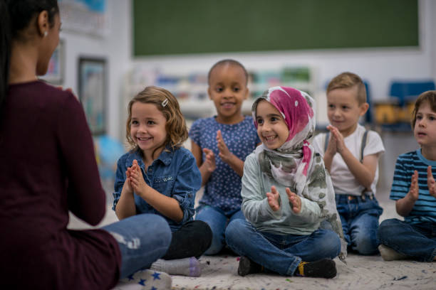 Children Clapping To A Song A multi-ethnic group of young school children are indoors in their classroom. They are sitting on the floor and clapping along to music with their teacher. They are smiling and having fun. immigrant stock pictures, royalty-free photos & images