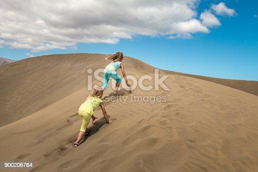 2 children climb a sand dune in the desert