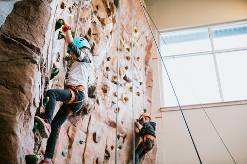 Boys and girls climb a large bouldering  wall at a rock climbing gym.  A fun and healthy way to stay active and physically fit.  Shot in Washington State, USA.