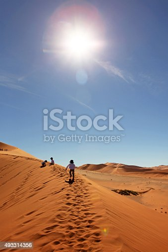 Three little boys are having fun climbing big sand dunes in Sossusvlei in Namibia on a warm sunny day. This is a vertical image of the Namib-Naukluft National Park landscape as seen when climbing a Big Mama dune.