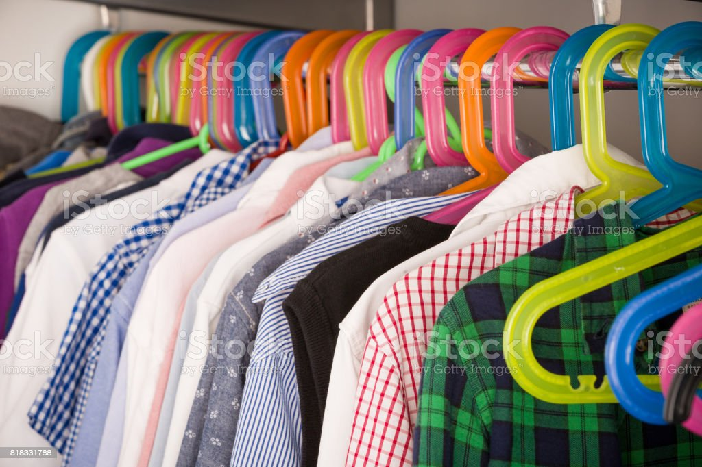Children clothes on hangers in a room. wardrobe with boy's clothes on hangers. Shopping and consumerism concept. Dressing closet with clothes arranged on hangers.Colorful wardrobe for kids. stock photo