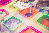Color pigments in plastic containers on a table. Children glue the dust on the paper, Dubna, Russia.