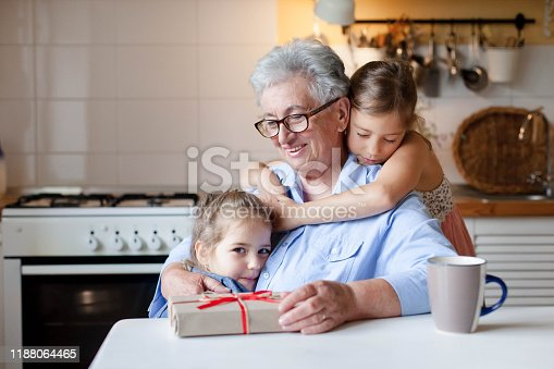494086690istockphoto Children congratulate grandmother with gift box. Kids are hugging senior woman 1188064465