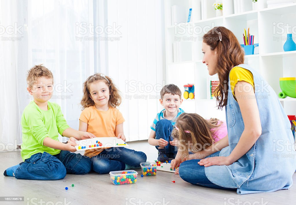 Children Creating Mosaic with color sticks stock photo