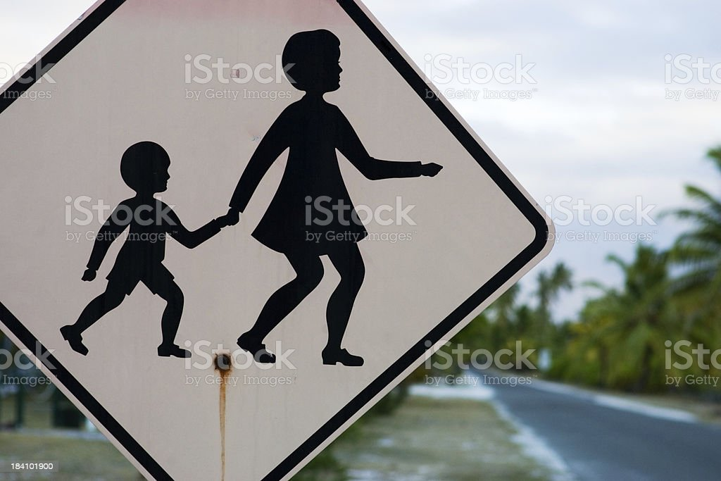 """children crossing sign """"children, school crossing sign on tropical island, rusty australian sign, black mother and child silhouette, pink background on a lonely topical road. palmtrees and street unsharp in the background."""" Australia Stock Photo"""