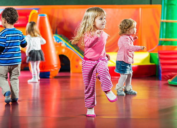Children dancing. Cute kids dancing in the playroom. Focus is on girl in the foreground.   2 3 years stock pictures, royalty-free photos & images
