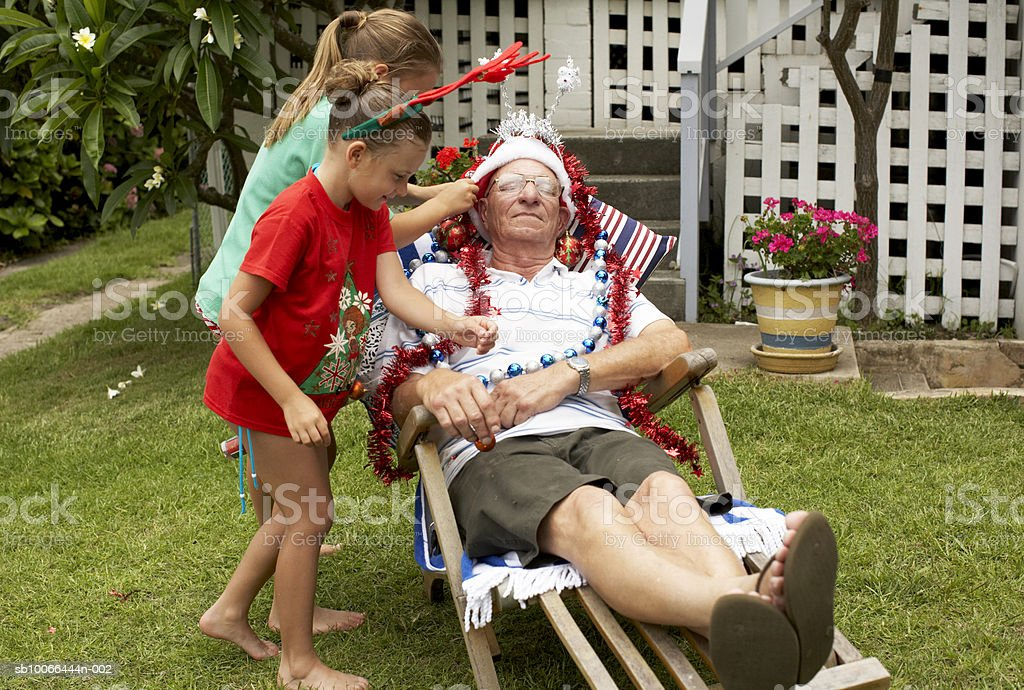 Children (7-9) decorating senior man with Christmas decorations in yard royalty-free stock photo