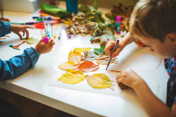 Children doing autumn handcrafts stock photo