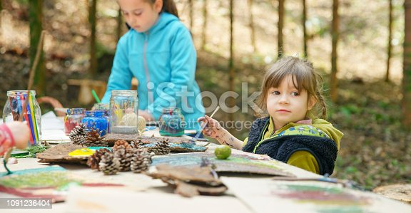 Girls doing drawing in forest.