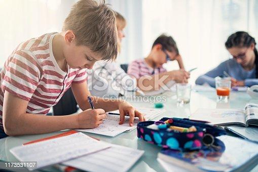862426824 istock photo Children doing homework at school 1173531107