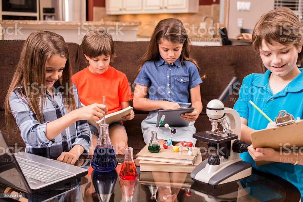Children doing science homework at home. royaltyfri bildbanksbilder