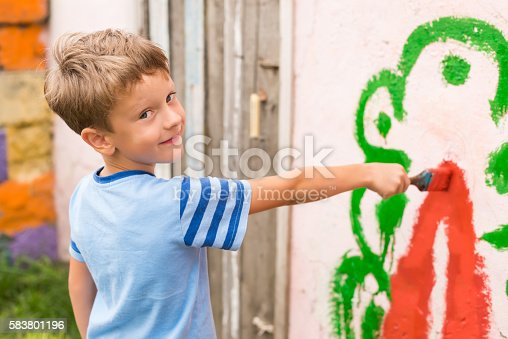 istock children draw a picture on the wall 583801196