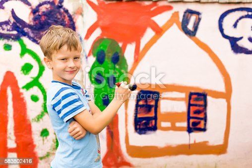 istock children draw a picture on the wall 583802416