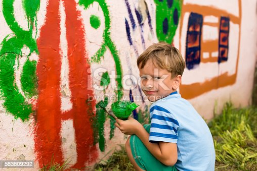 istock children draw a picture on the wall 583809292