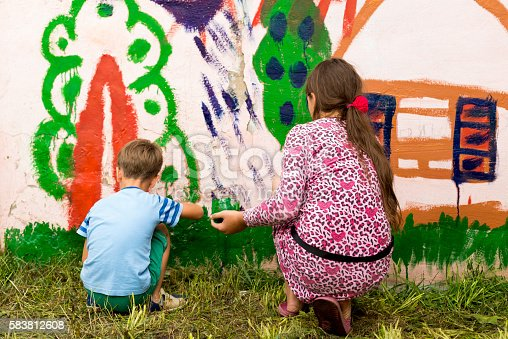 istock children draw a picture on the wall 583812608