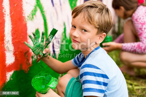 istock children draw a picture on the wall 583813602