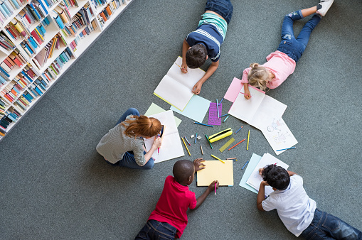 Elementary children lying on the floor and drawing at library.Top view of five multiethnic boys and girls in daycare house drawing on copybook. High angle view of group of kids drawing with colorful pencils on floor.