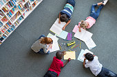 Elementary children lying on the floor and drawing at library. Top view of five multiethnic boys and girls in daycare house drawing on copybook. High angle view of group of kids drawing with colorful pencils on floor.