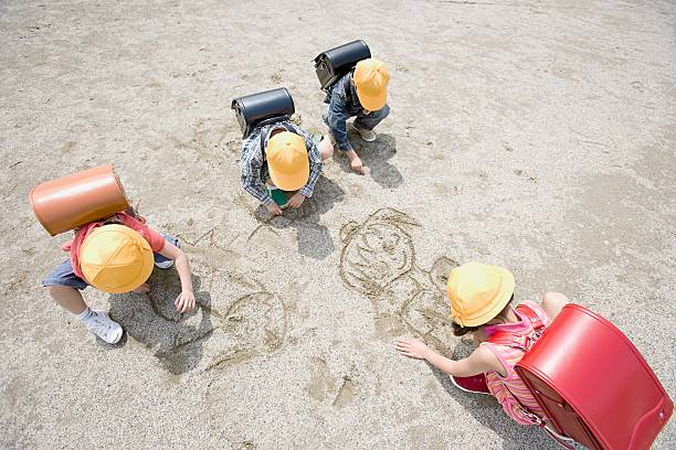 Children drawing in the sand stock photo