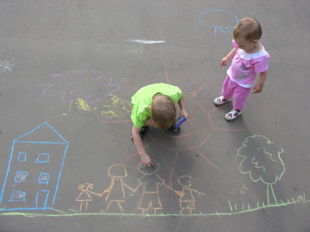 children drawing on asphalt family house stock photo