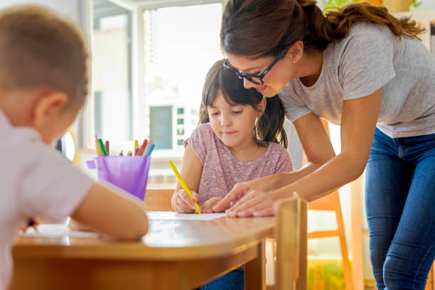 children drawing with smiling preschool teacher assisting them - preschool stock photos and pictures