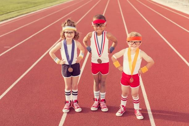 enfants habillés comme ringards de piste portant des médailles - match sport photos et images de collection