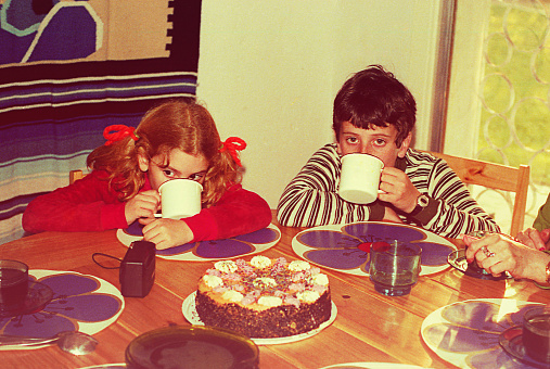 Vintage image of a boy and a girl drinking hot chocolate with a table