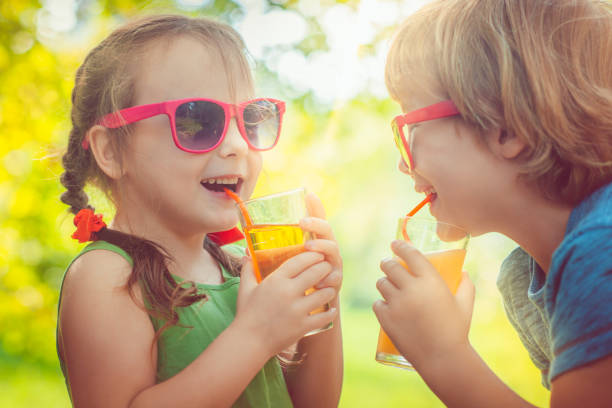 children drinking juice - cold drink stock photos and pictures