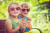 Happy boy and girl drinking juice outdoors in summer