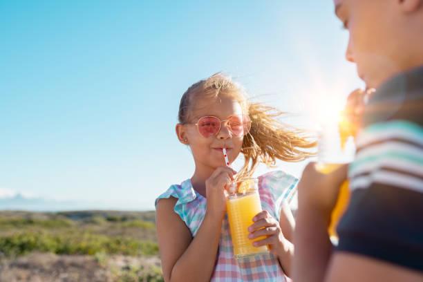 kinderen drinken orange juice outdoor - sapjes stockfoto's en -beelden